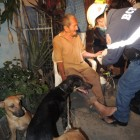 Walter Rodriguez receives medical care by local firefighters while his dogs Muñeco, Laica and Chiquita sit nearby. Photo Credit: Marcelo Gutierrez