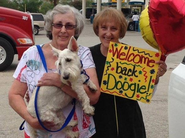 Linda Davis - mom - happily reunited with her Doogie, as Cheri proudly holds up the welcome home sign.