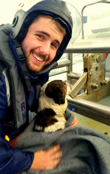 Able Seaman Combat Specialist Damien Willis gives the dog a much-needed warm snuggle.