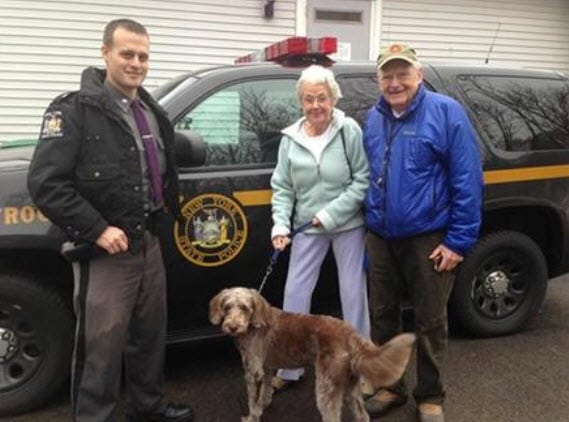 State Trooper Kevin Lund, Belle, and the dog's owners.  Photo Credit: State Police